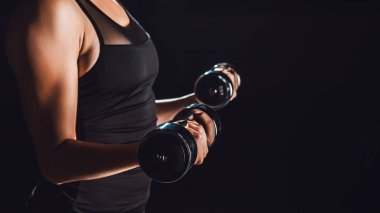 partial view of female bodybuilder working out with dumbbells, black background