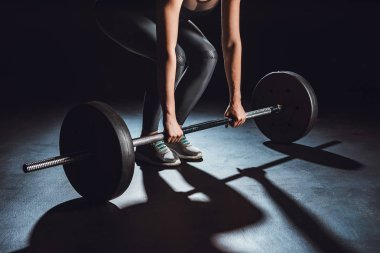 cropped image of female athlete working out with barbell, black background
