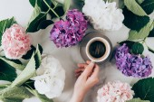 flat lay with hortensia flowers and female hand with cup of espresso coffee
