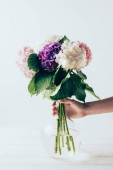 Fotografie partial view of woman holding vase with pink, white and purple hydrangea flowers, on white