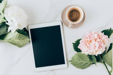 top view of hortensia flowers, coffee and digital tablet with blank screen on marble surface