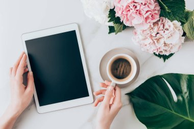 cropped view of woman hand with coffee cup and digital tablet with blank screen on tabletop with hortensia flowers
