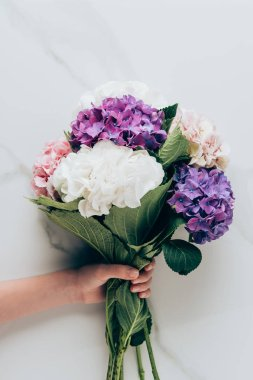 cropped view of woman holding bouquet of hortensia flowers on marble surface