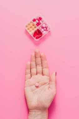 cropped shot of woman holding pink pill on pink surface with plastic container for medicines
