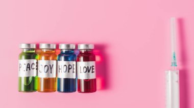 top view of syringe and bottles with love, hope, joy and peace vaccine signs in row on pink tabletop