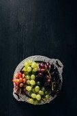 top view of various types of grapes on vintage plate on black wooden surface