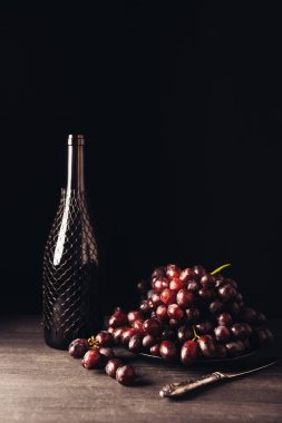 fresh ripe red grapes on plate, vintage knife and bottle of wine on wooden table on black