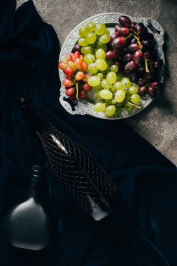 top view of various types of grapes on vintage plate and bottles of wine on dark fabric