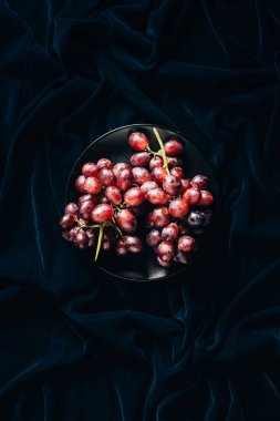 top view of fresh ripe juicy red grapes on black plate on dark fabric