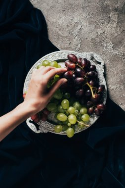 partial top view of person eating delicious grapes from vintage plate