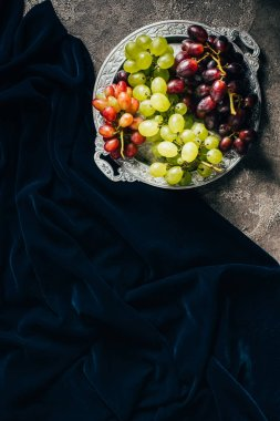 top view of vintage plate with various types of grapes and dark fabric with copy space