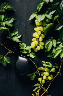 top view of fresh white grapes with green leaves and bottle of wine on dark wooden surface