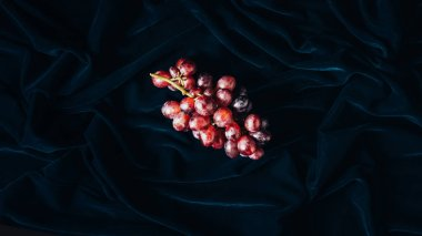 top view of fresh ripe red grapes on dark fabric