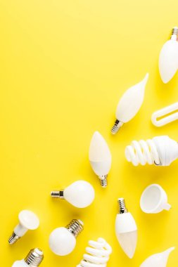 Top view of various types of light bulbs on yellow background stock vector