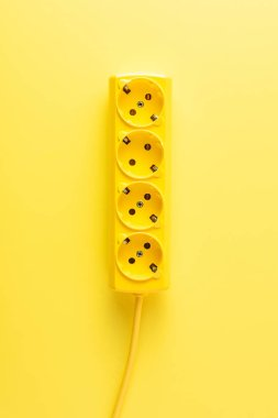 close-up view of bright yellow socket outlet on yellow background