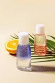 Chiuda sulla vista di acqua micellare in bottiglie, foglia di Palma verde e arancione metà con acqua scende su sfondo beige