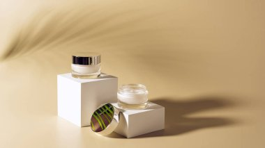 close up view of palm leaf shade, facial and body creams in glass jars on white cubes on beige background