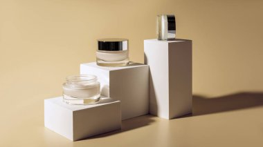 close up view of facial and body creams in glass jars on white cubes on beige background