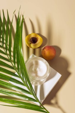 top view of body cream, apricots and green palm leaf on beige background