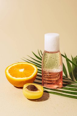 close up view of micellar water for skin care in bottle and orange half on beige background