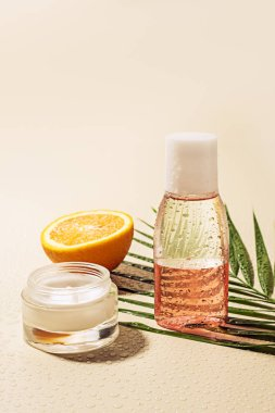 close up view of facial cream and lotion, palm leaf and orange half with water drops on beige background