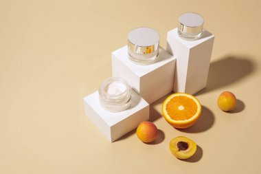 close up view of arranged skin care creams and fruits on beige backdrop