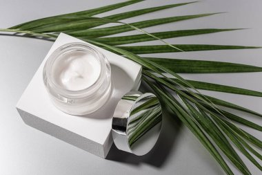 Top view of moisturizing cream in glass jar with palm leaf on grey background stock vector
