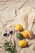 Fotografie high angle view of sunglasses, flowers and string bag with tropical fruits