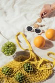 cropped shot of human hand, earrings, sunglasses and string bag with fresh fruits