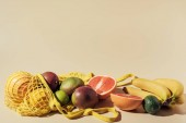 Fotografie close-up view of fresh ripe tropical fruits and string bag on brown