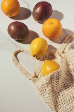 top view of string bag with fresh ripe tropical fruits on white