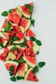 Fotografie top view of red juicy watermelon and lime slices with mint leaves, on grey background