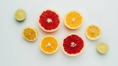 top view of fresh grapefruit, lemon, lime and orange slices, on grey