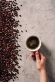 cropped shot of woman holding cup of coffee on concrete surface with spilled coffee beans