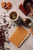Fotografie Draufsicht der Cup und Cezve Kaffee mit Buch und Kaffee Mühle auf Betonoberfläche