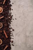 Fotografie Draufsicht der verschütteten Kaffee-Bohnen mit verschiedenen Gewürzen auf Betonoberfläche