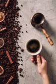 Fotografie zugeschnittenen Schuss Frau mit Tasse Kaffee auf der Betonoberfläche mit verschüttetem Kaffee Bohnen und Gewürzen