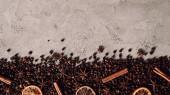 Fotografie Draufsicht der verschüttete Kaffeebohnen mit trockenen Gewürzen auf Betonoberfläche