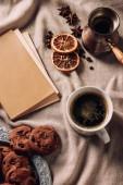 Fotografie Draufsicht der Tasse Kaffee mit Buch und Schokoladenkekse auf Beige Stoff