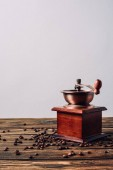 vintage coffee grinder with coffee beans on rustic wooden table