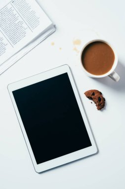 Top view of tablet with coffee cup and bitten chocolate chip cookie on white surface stock vector