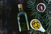 top view of bottle of olive oil and olives in bowls on shabby surface