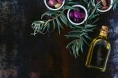 Fotografie pohled shora různých oliv a láhev oleje na omšelé povrchu