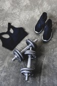 Fotografie high angle view of dumbbells with sneakers and sport bra on concrete surface