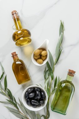top view of olive oil in glass bottles and tasty olives on marble table