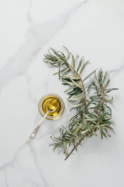 top view of olive oil and spoon in glass on marble table