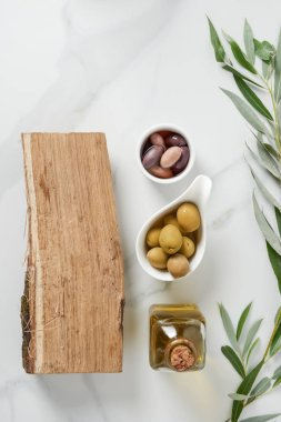 elevated view of bottle of olive oil, log and olives in bowls on marble table