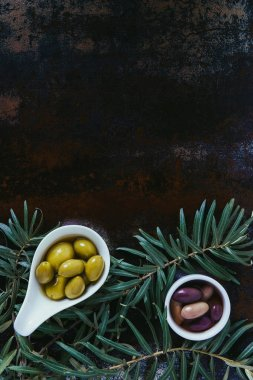 elevated view of olives and twigs on shabby surface