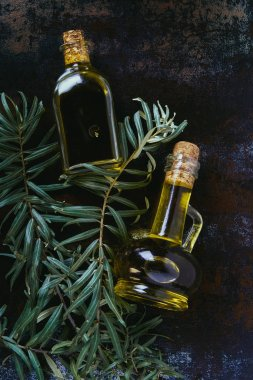 top view of two bottles of olive oil and twigs on shabby surface