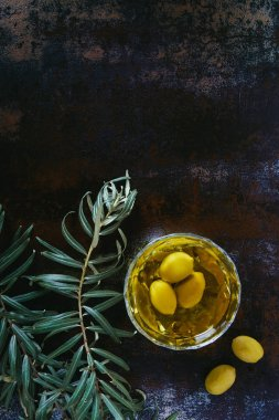 top view of olive oil and olives in glass on shabby surface